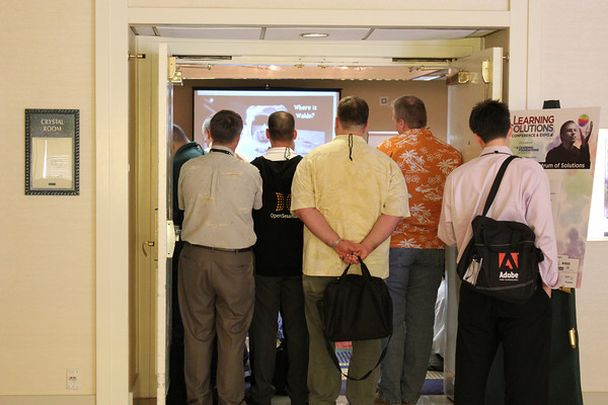 photo of several people outside a session room looking in