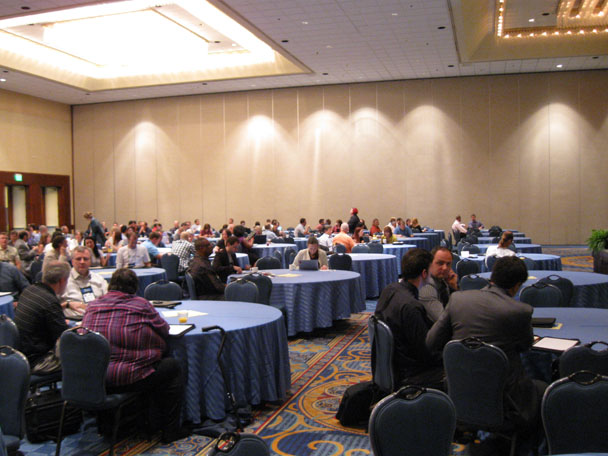photo of a session room with lots of people around rounded tables