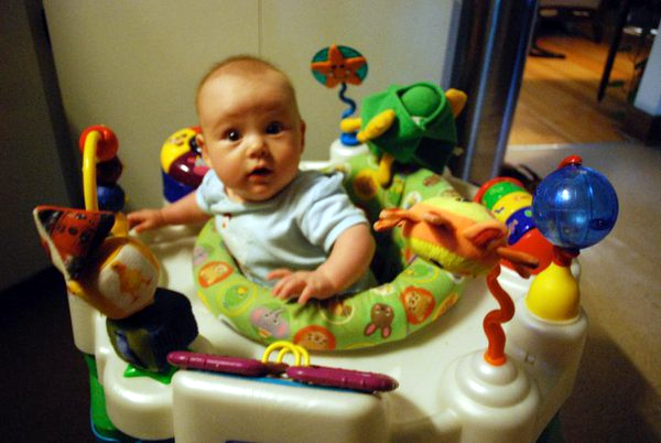 A baby in a mobile chair surrounded by toys
